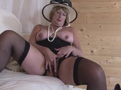 This old mature is wearing her fancy hat and she has her legs spread so she can plays with her pussy