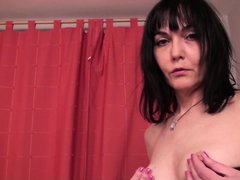 This mature brunette in in the bedroom wearing only a sexy black lingerie. She takes off her bra so