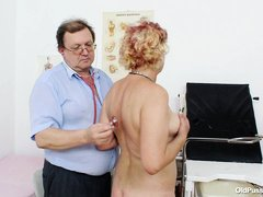 This mature lady is completely naked before his doctor and the doctor starts examining her big breas